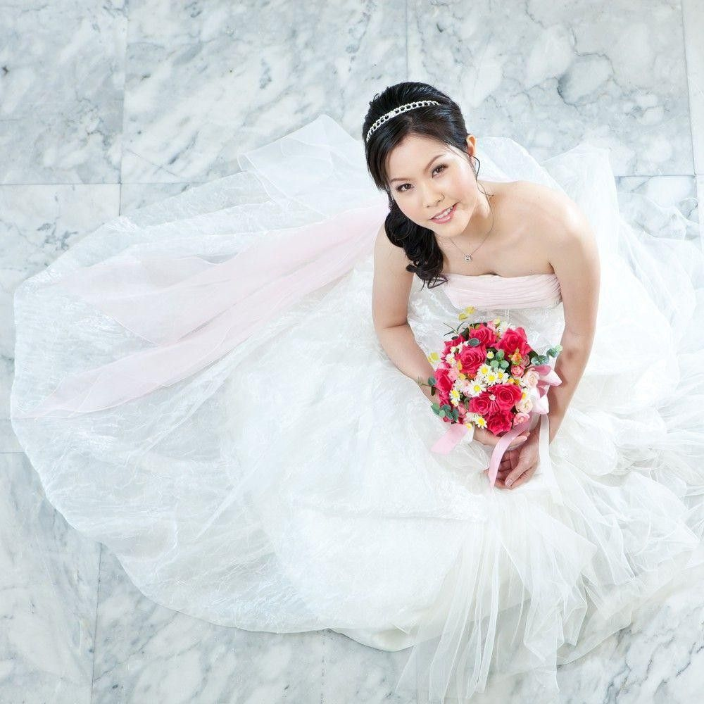 Asian bride in a white dress looking up