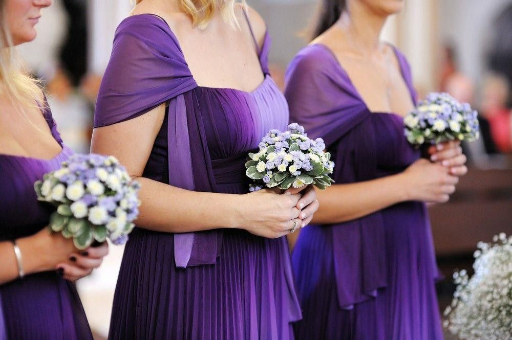 Bridesmaids in purple dresses holding a bouquet
