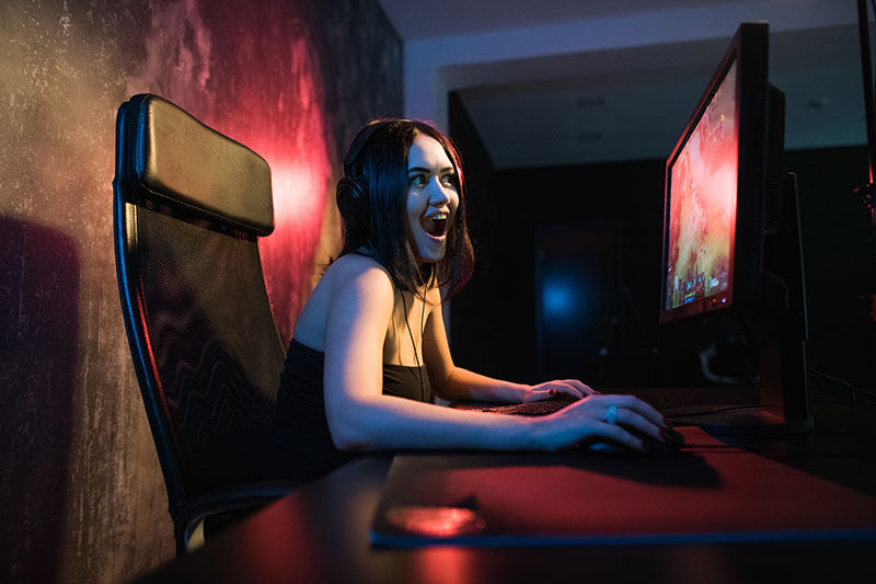 A cute female gamer girl sits in a cozy room behind a computer and plays games. Woman live streaming computer video games to her fans and wiggle hand to them. Streamer and gamer concept