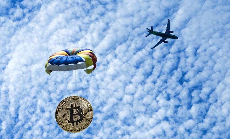Coin bitcoin is flying on a parachute from the plane. Airdrop token. Free distribution of BTC.