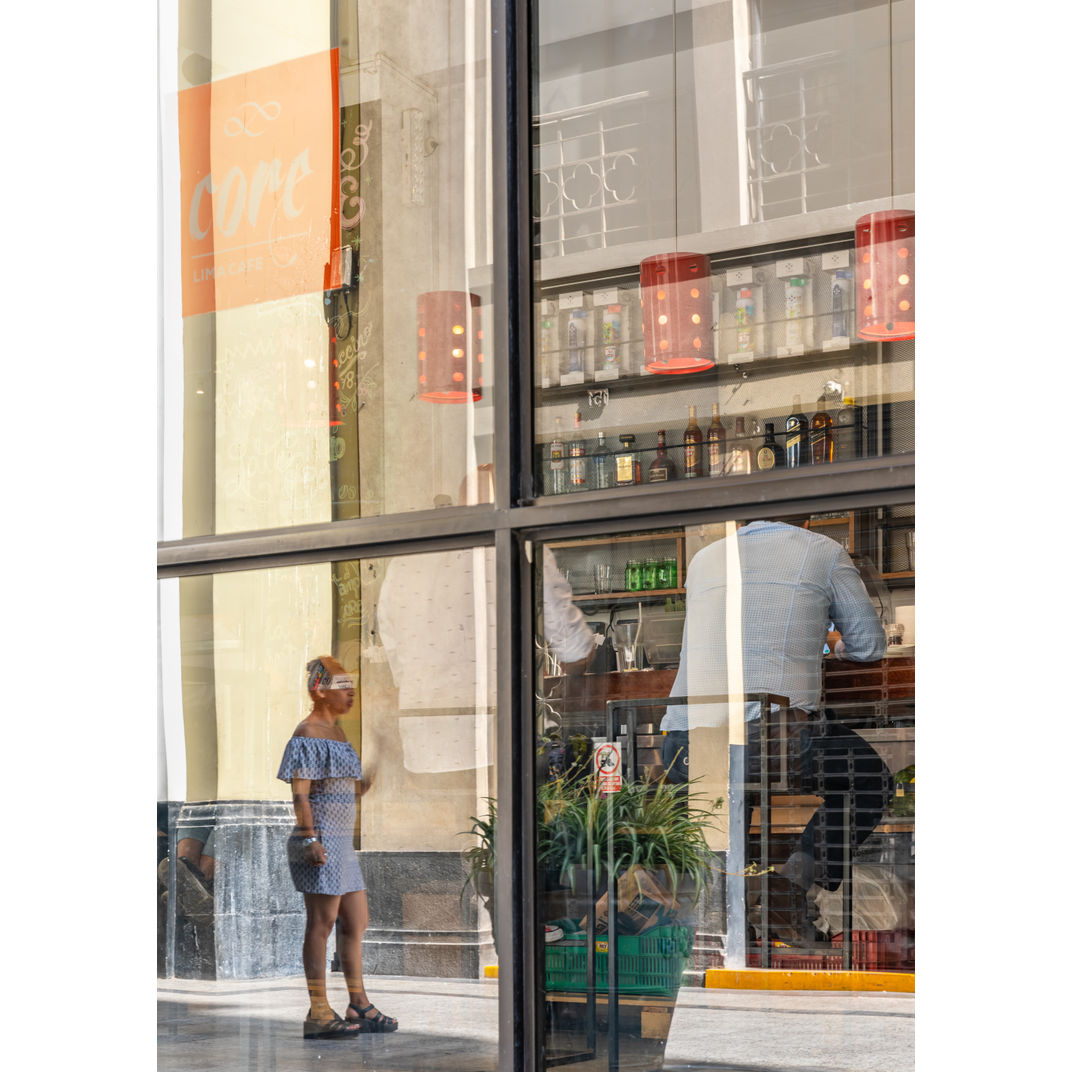 Woman smoking reflected on a coffee shop glass in Lima's downtown. by Romulo TIJERO