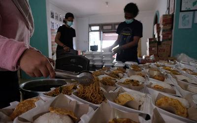 Sejumlah relawan menyiapkan porsi makanan siap saji di kafe yang dirubah menjadi dapur umum bernama ...