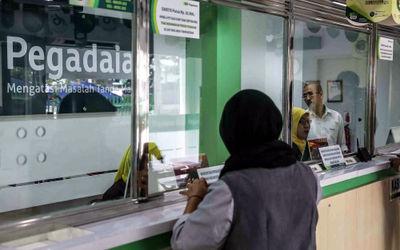 Petugas melayani warga saat melakukan transaksi di gerai pegadaian Jakarta. Foto: Ismail Pohan/TrenA...