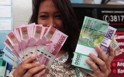 Warga menunjukkan uang kertas rupiah baru tahun emisi 2016 usai melakukan penukaran di pusat perbela...