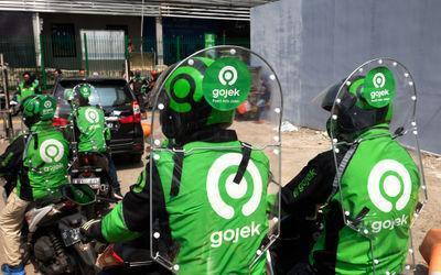 Pengemudi GoRide menggunakan sekat pelindung saat uji coba penggunaannya pada armada Gojek di Jakart...