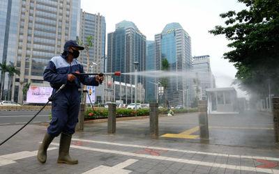 Petugas melakukan penyemprotan disinfektan saat pemberlakuan kembali PSBB di Jalan Sudirman, Jakarta...