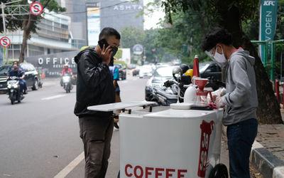 Ubaid (25) membuatkan pesanan kopi pelanggannya di kawasan Senopati, Jakarta Selatan, Rabu, 21 Oktob...