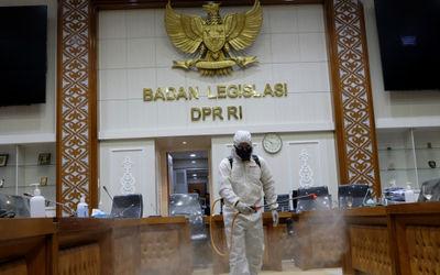 Petugas melakukan penyemprotan disinfektan di ruang rapat badan legislasi Gedung Nusantara 1, Komple...