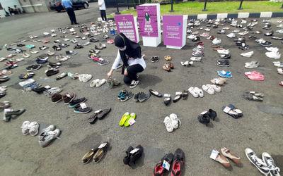 Pegiat komnas perempuan memegang sepatu saat aksi diam '500 Langkah Awal Sahkan Rancangan Unda...