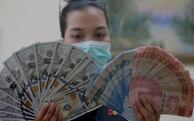 Karyawati menunjukkan mata uang Rupiah dan Dolar di salah satu tempat penukaran uang atau Money Chan...