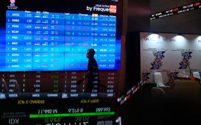 Karyawan melintas dengan latar belakang layar pergerakan Indeks Harga Saham Gabungan (IHSG) di gedun...