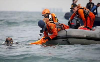 Anggota Tim SAR Gabungan menggunakan perahu karet saat melakukan pencarian korban dan puing pesawat ...