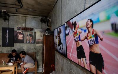 """Pengunjung berada diantara karya pewarta foto yang dipajang di kedai kopi """"Ngopi di Halaman&#8..."""
