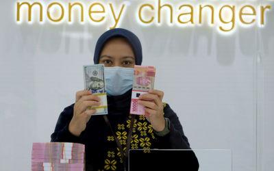 Karyawati menunjukan mata uang Rupiah dan Dolar AS di Jakarta, Kamis, 18 Februari 2021. Foto: Ismail...