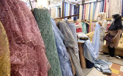 Pembeli memilih bahan kain di kios blok tekstil Pasar Tanah Abang, Jakarta, Rabu, 31 Maret 2021. Fot...