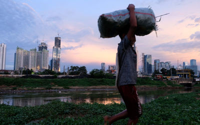 Warga beraktivitas dengan latar belakang gedung bertingkat di kawasan Kebon Melati, Tanah Abang, Jak...