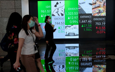 Karyawan melintas dengan latar layar pergerakan indeks harga saham gabungan (IHSG) di Gedung Bursa E...