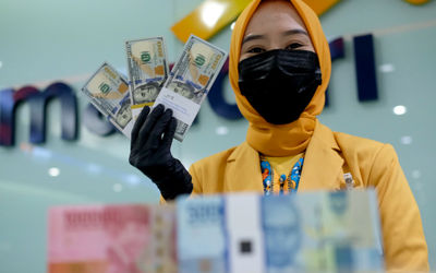 Karyawati menunjukkan mata uang rupiah dan dolar di kantor cabang Bank Mandiri, Jakarta, Senin, 22 M...