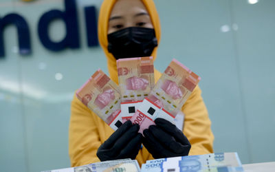 Karyawati menunjukkan mata uang rupiah dan dolar di kantor cabang Bank Mandiri, Jakarta, Senin, 22 Maret 2021. Foto: Ismail Pohan/TrenAsia\n