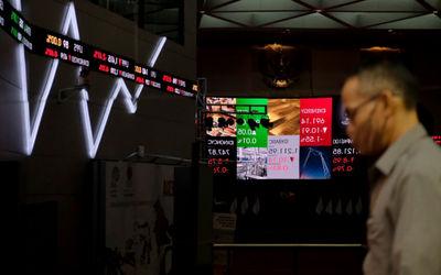 Karyawan beraktivitas dengan latar pergerakan indeks harga saham gabungan (IHSG) di Gedung Bursa Efe...