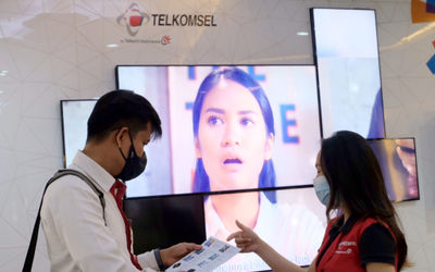 Karyawan melayani pelanggan di gerai GraPARI Telkomsel yang berada di salah satu pusat perbelanjaan ...