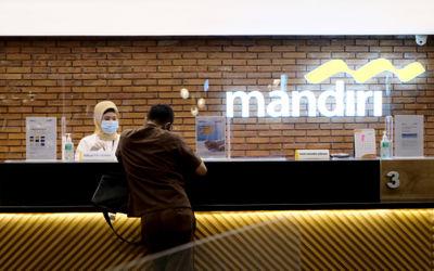 Karyawan melayani nasabah di gerai salah satu cabang Bank Mandiri, di Jakarta, Selasa, 6 April 2021. Foto: Ismail Pohan/TrenAsia\n