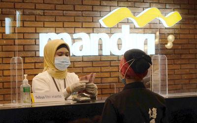 Karyawan melayani nasabah di gerai salah satu cabang Bank Mandiri, di Jakarta, Selasa, 6 April 2021....