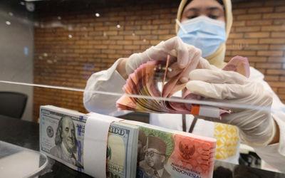Karyawati menghitung uang di gerai salah satu cabang Bank Mandiri, di Jakarta, Selasa, 6 April 2021....