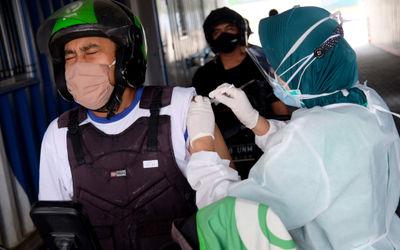 Petugas nakes menyuntikkan dosis vaksin kepada driver Go Ride pada vaksinasasi untuk mitra driver Go...