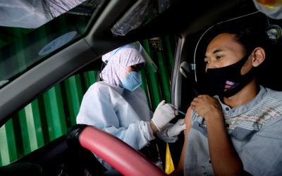 Petigas menyuntikkan dosis vaksin kepada driver Gocar pada vaksinasasi untuk mitra driver Gojek di K...