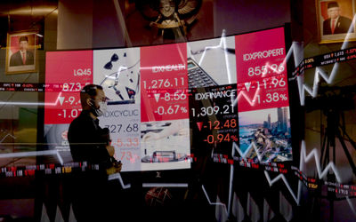 Awak media beraktivitas dengan latar layar pergerakan indeks harga saham gabungan (IHSG) di gedung B...