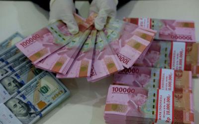 Karyawati salah satu bank menunjukkan mata uang Rupiah dan Dolar di Jakarta, Selasa, 8 Juni 2021. Fo...