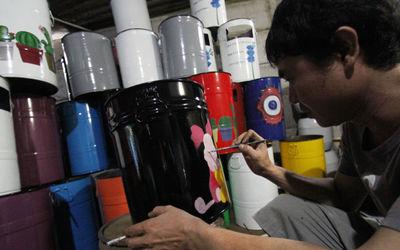 Nampak sorang perajin tengah membuat lukisan tong sampah dengan gambar karakter untuk membuat tampil...