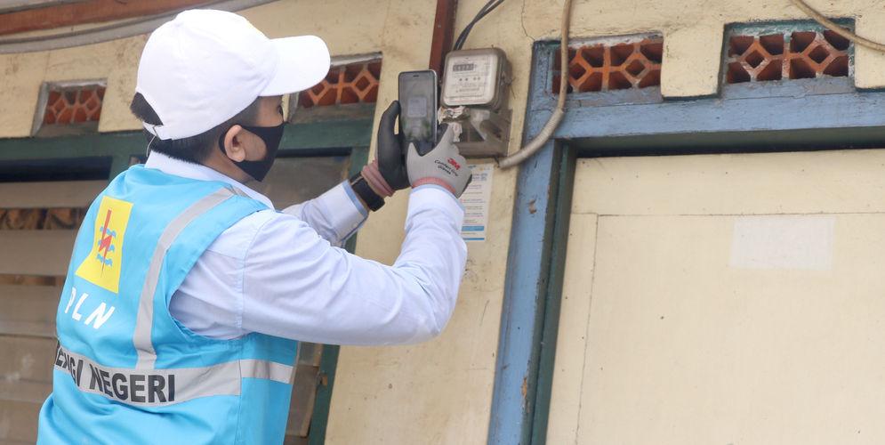 Petugas PLN merekam pencatatan meteran listrik di rumah warga kawasan Kebayoran Baru, Jakarta, Selasa 30 Juni 2020. PLN memastikan seluruh petugas pencatatan meter mendatangi langsung rumah pelanggan pascabayar untuk digunakan sebagai dasar perhitungan tagihan listrik bulan Juli 2020. Foto: Ismail Pohan/TrenAsia\n