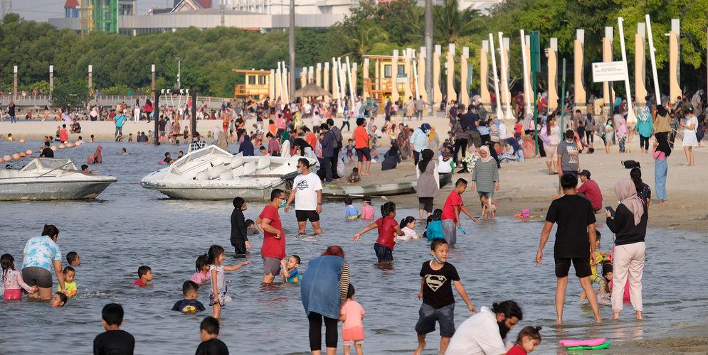 Wisatawan menikmati waktu berlibur di Pantai Lagoon, Taman Impian Jaya Ancol, Jakarta, Kamis, 29 Oktober 2020. Foto: Ismail Pohan/TrenAsia\n