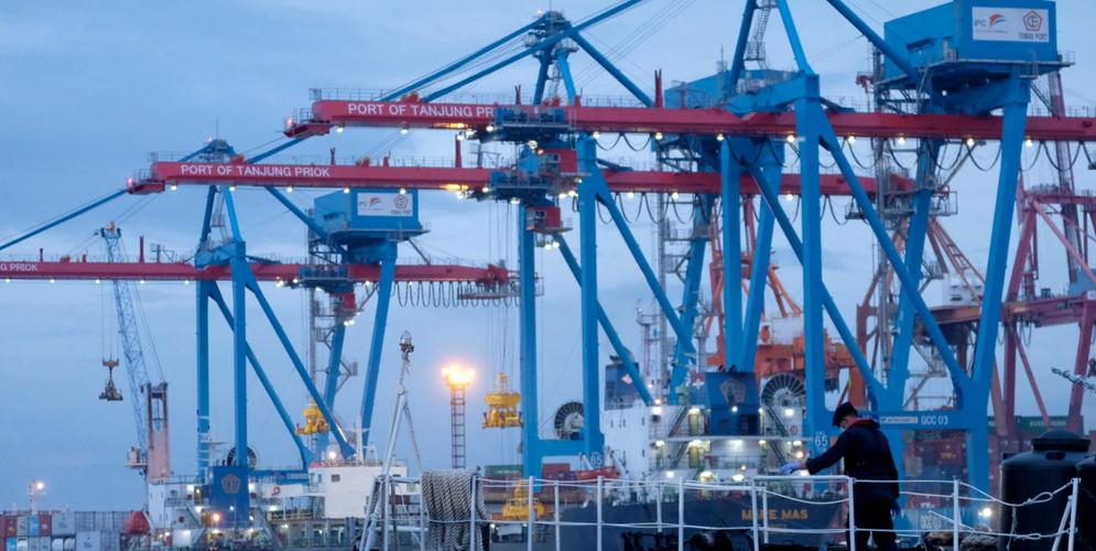 Kapal melintas didekat crane bongkar muat peti kemas di dermaga Pelabuhan Tanjung Priok, Jakarta, Senin, 11 Januari 2021. Foto: Ismail Pohan/TrenAsia\n