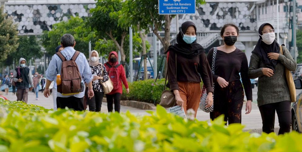 Pekerja melintas pada jam pulang kerja di kawasan Jalan Jenderal Sudirman, Jakarta, Senin, 22 Februari 2021. Foto: Ismail Pohan/TrenAsia\n