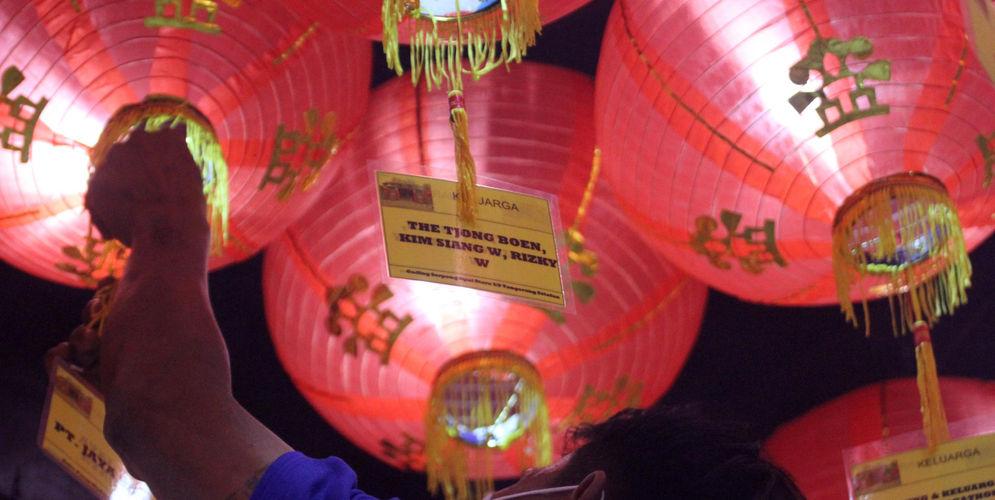 Petugas merapikan lampion pada malam perayaan Tahun Baru Imlek 2572 di Vihara Nimmala Boen San Bio, Pasar Baru, Tangerang, Banten, Kamis, 11 Februari 2021. Foto: Panji Asmoro/TrenAsia\n