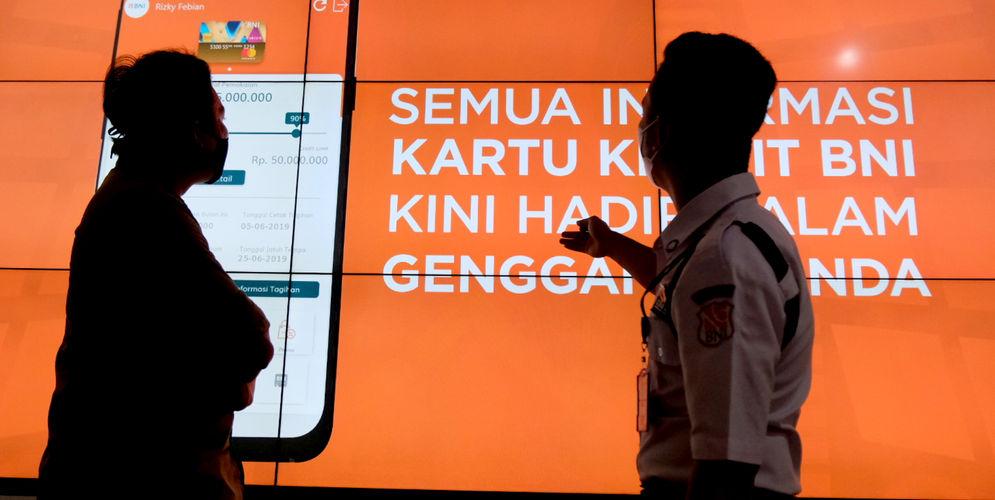 Nasabah mendapatkan penjelasan dari petugas di gerai BNI Digital Branch Gandaria City, Jakarta, Kamis, 4 Maret 2021. Foto: Ismail Pohan/TrenAsia\n