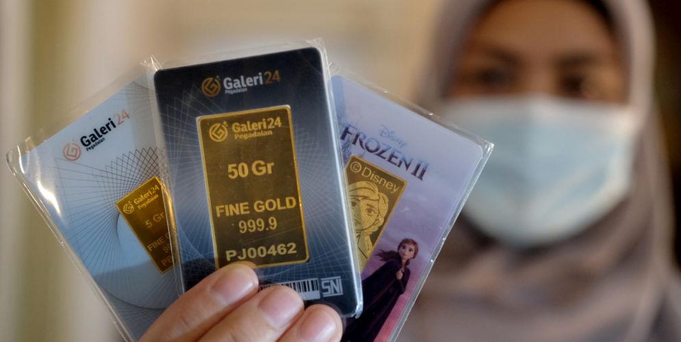 Karyawati menunjukkan emas batangan di gerai Galeri 24 Pegadaian, Jakarta, Senin, 1 Maret 2021. Foto: Ismail Pohan/TrenAsia\n