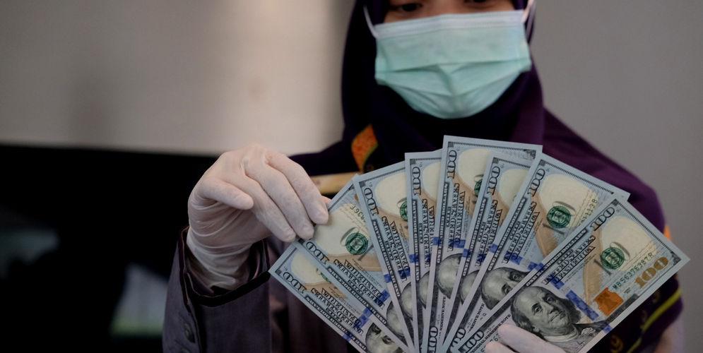 Karyawati menunjukkan mata uang Dolar Amerika di salah satu teller bank, di Jakarta, Rabu, 3 Maret 2021. Foto: Ismail Pohan/TrenAsia\n