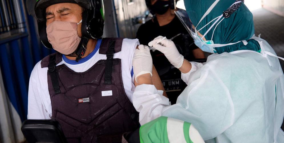 Petugas nakes menyuntikkan dosis vaksin kepada driver Go Ride pada vaksinasasi untuk mitra driver Gojek di Kemayoran, Jakarta, Kamis, 29 April 2021. Foto: Ismail Pohan/TrenAsia\n