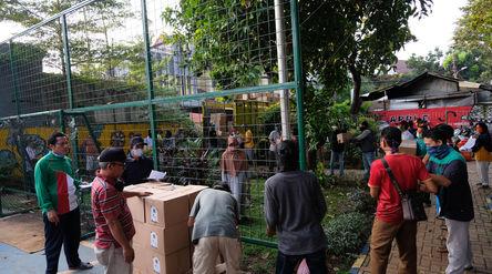 Warga bergotong-royong menurunkan paket sembako yang akan di bagikan kepada warga RW.04 Kelurahan Ja...