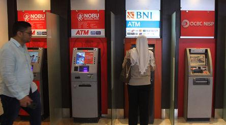 Warga menggunakan fasilitas anjungan tunai mandiri (ATM) di salah satu pusat perbelanjaan di Jakarta...