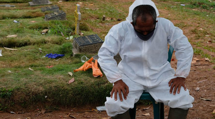 Petugas Suku Dinas Pertamanan dan Pemakaman mengenakan perlengkapan APD beristirahat di area blok kh...