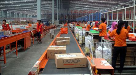 Pekerja menyiapkan barang pesanan untuk dikirimkan kepada pembeli di gudang toko daring Lazada di Ci...