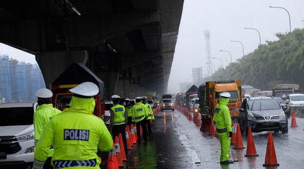 Petuga kepolisian berjaga di pos penyekatan kendaraan melalui Tol Jakarta-Cikampek Km 31 di Cikarang...