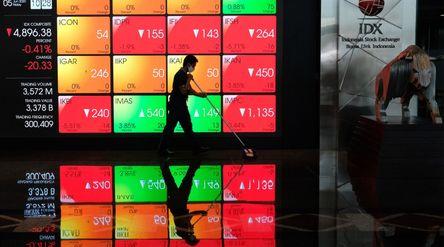 Pekerja beraktifitas dengan latar belakang layar monitor pergerakan Indeks Harga Saham Gabungan (IHS...