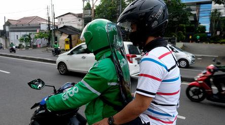 Driver Grab Bike mengenakan Grab Protect pelindung yang membatasi antara pengemudi dan penumpang saa...