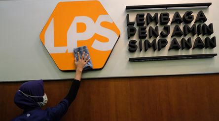 Karyawan membersihkan logo Lembaga Penjamin Simpanan (LPS) di Jakarta, Jum'at, 10 Juli 2020.  ...